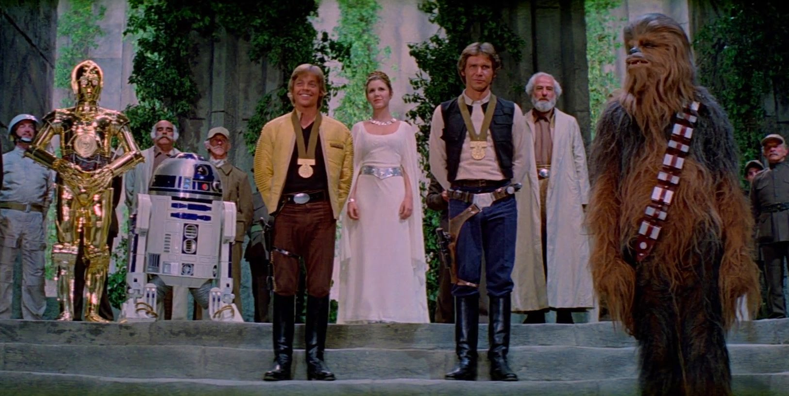 C3-PO, R2D2, Luke Skywalker, Princess Leia Organa, Han Solo & Chewbacca, the Wookie at the end of Star Wars IV A New Hope.